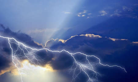 discharge: Solar ray illuminates the dark thunderstorm clouds, struck by the high-current discharge of lightning.