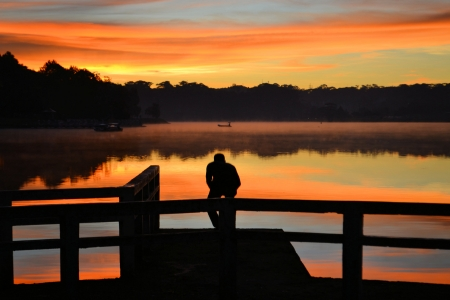 lost lake: A hopeless person standing alone at a lakefront contemplating life.