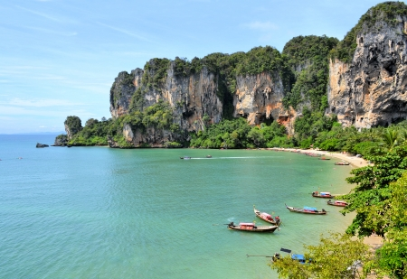 Ton Sai Beach on a sunny day with longtail boats as soon from a climbing wall