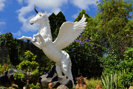 statue of a unicorn jumping with its front hooves in a forest in Dalat, Vietnam photo