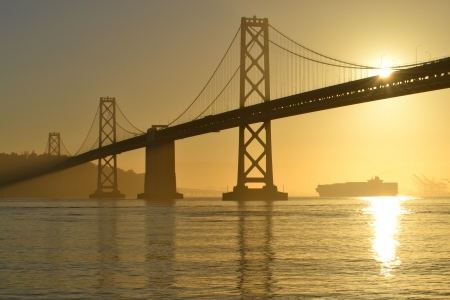 sf: Bay Bridge at Sunrise with a container ship in the distance, San Francisco, California Stock Photo