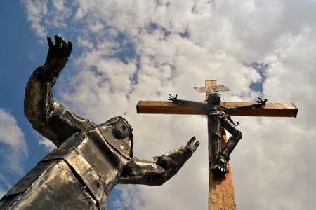 martyr: Modern steel statue of Christ with Virgin Mary lying at his feet against blue sky Stock Photo