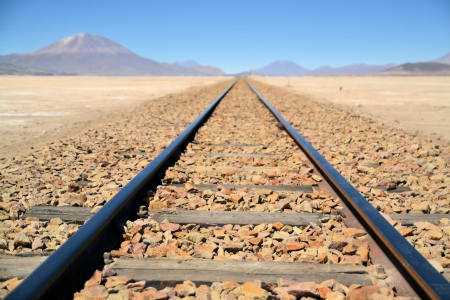 Endless train tracks in the desert with a volcano in the distance, Bolivia, South America