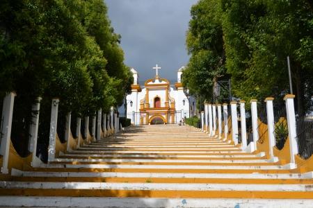 A Christian Catholic chapel on a hill with colorful steps in San Cristobal de las Casas, Chiapas, Mexico