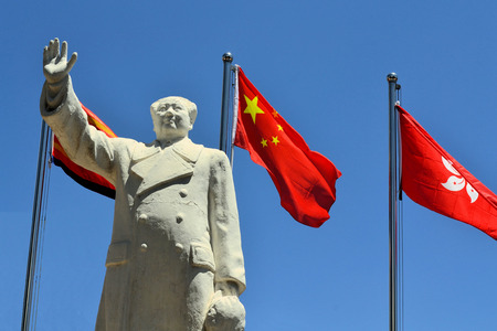 chairman: A Statue of Chinas former Chairman Mao Zedong with Chinese flagin the city of Lijang, China