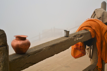 A Hindu Pilgrim is taking a morning bath in the holy river Ganges in VaranasiBenares on a misty day photo