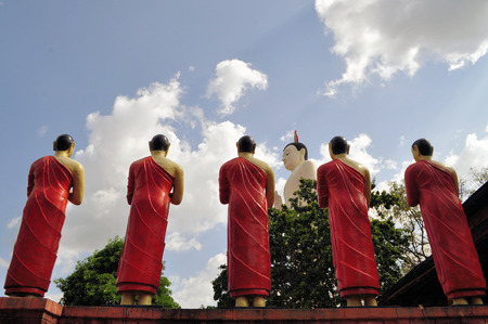 5 statues of Buddhist monk disciples called Arahants praising a Buddha statue photo