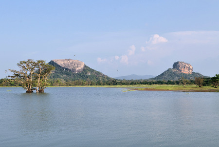 Human made tank, Pidurungala rock and Sigiriya Lion Rock Fortress in Sri Lanka, so-called 8th wonder of the world and former monastery photo