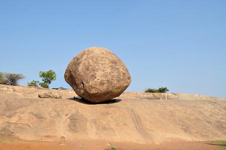 Krishnas butterball balancing giant natural rock stone.  Stock Photo