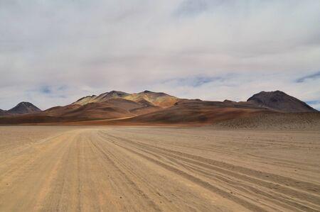 Lonely unpaved road trough colorful Salvador Dali Desert in Altiplano, Bolivia
