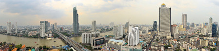the skyline of Thailands capital Bangkok with itS Chao Phraya river as seen from the Sathorn Unique abandoned skyscraper photo