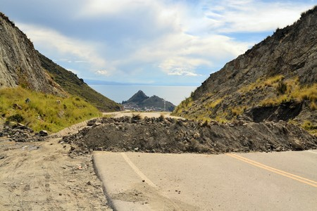 mud slide: Road at lake Titicaca is blocked by rock and debris for political reasons on the altiplano near Copacabana, Bolivia