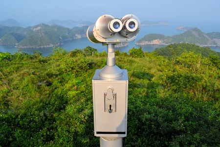 cat island: Coin operated telescope binoculars at a scenic lookout on the Vietnamese island Cat Ba, overlooking karst limestone rock islands in Halong Bay in the South China Sea