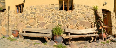 inca architecture: Wooden bench in front of a home in Inca style architecture in the sacred valley between Machu Picchu and Cuzco in the old town of Ollantaytambo in the Andes mountains, Peru