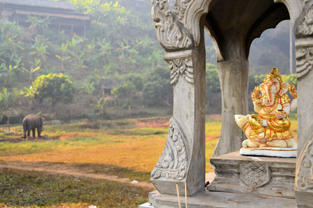 a righteous person: Sitting Ganesha statue in a shrine with elephant in background in Northern Thailand, Ganesha is a Hindu god and the remover of obstacles and is also revered in Thailand.