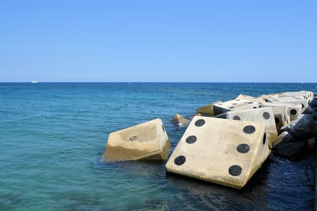 berm: Coastline with concrete wave breaker in the shape of dice at Barceloneta beach pier, Mediterranean, Barcelona, Spain