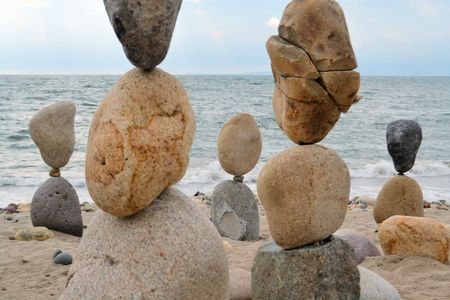 pyramidal: Rocks and Pebbles towers balanced in Zen style at the shores of the ocean Stock Photo