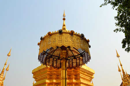 stupa one: Golden umbrella in front of a golden stupa at one of the Buddhist Wat temples in Chiang Mai, Thailand