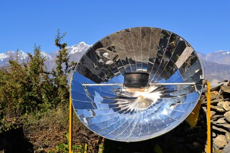 A kettle with tea water is boiled using a solar parabolic reflector above Sera Monastery in Lhasa, Tibet
