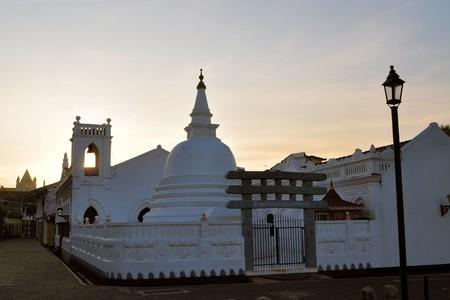 shri: Christian All Saints Anglican church and Fort Shri Sudarmalaya Buddhist temple with stupa at sunrise at ancient Dutch Galle Fort, coast of Sri Lanka island, South Asia Stock Photo