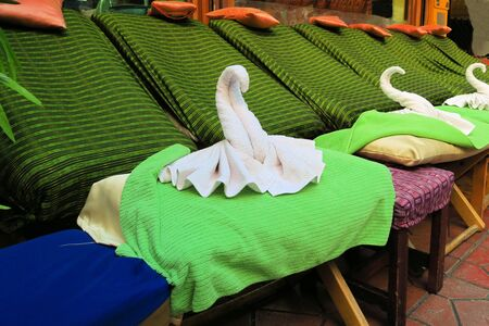 singing bowl massage: Spa massage setting with thai massage chairs and towel in swan form
