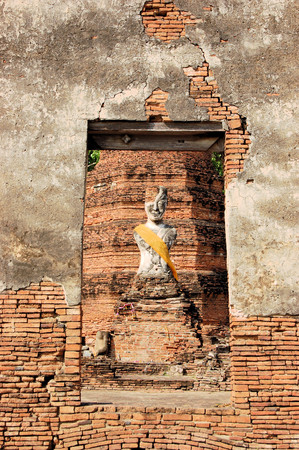Half ruined Buddha statue at an Ancient temple in Ayutthaya former capital of Thailand photo