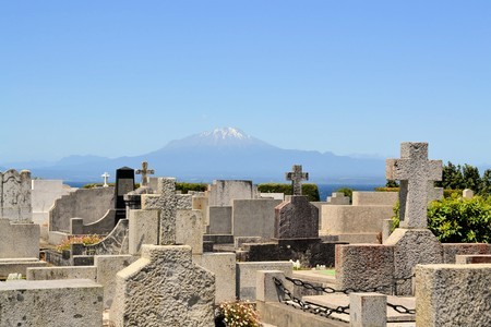 immigrants: Cemetary of German immigrants with Volcano Calbuccowith lake Llanquihue seen from Puerto Varas, Patagonia, Chile Stock Photo