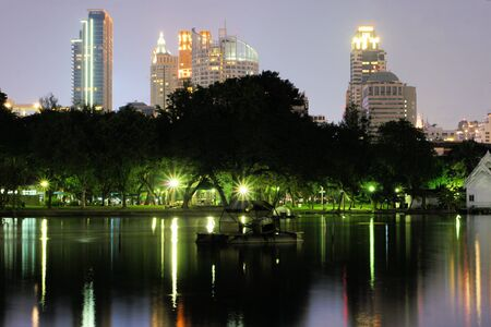 Business district cityscape from a park with Twilight Time from Lumpini Park, Bangkok, Thailand photo
