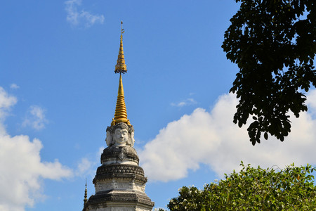Buddhas Face looks in all cardinal directions from a Stupa at a Buddhist temple, Chiang Mai, Thailand photo