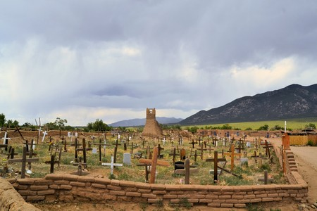 adobe pueblo: Christian cemetary in Taos Pueblo ancient Indian indegineous adobe city in New Mexico Stock Photo