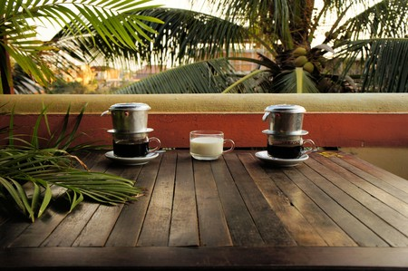 Coffee dripping in Vietnamese style with milk Ca Phe Sua under palm trees