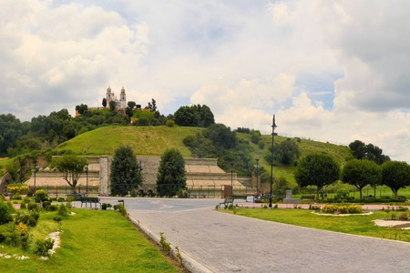 indios: Cholula, the largest pyramid ever build by man looks like a green hill with a church on top near Puebla in Mexico