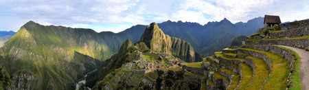 Panorama of Machu Picchu terraces, watcher's hut and Wuayna Picchu with shadow in early morning light. Machu Picchu is the famous lost city of the Incas near the river Urubamba located in the region of the sacred valley of Cuzco. Machu Picchu is a UNESCO