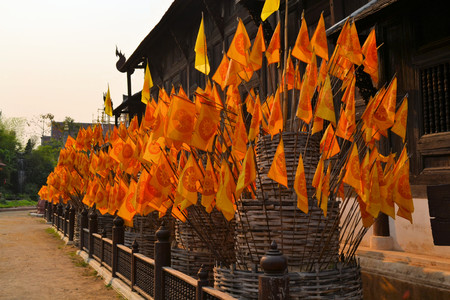 Orange Flags showing the Buddhist Wheel of life Dharmachakra in front of a temple, Chiang Mai, Thailand photo