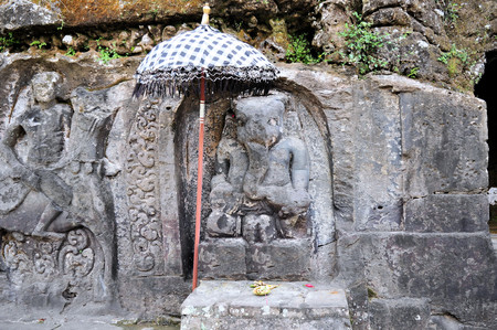 cliff face: Yeh Pulu is a famous carved cliff face dating back to the 15th century depicting daily scenes in Ubud, Bali, Indonesia Stock Photo