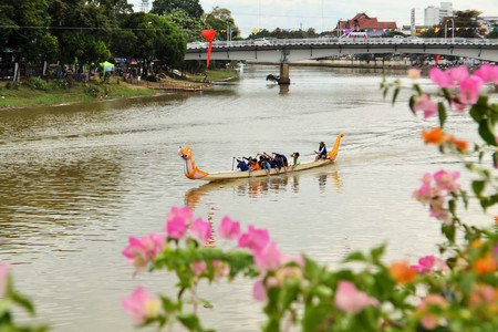 Chiang Mai, Thailand - 16 November 2013: A team of paddlers participate in a dragon boat race during the Loi Krathong festival on Ping River in Chiang Mai, Thailand
