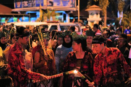 Yogyakarta, Indonesia - 7 October 2014:  258th city anniversary - One man helps another man reigniting his flame so he can march in a parade to celebrate tradition and unity at Marlioboro Street, Kota Yogyakarta Editorial
