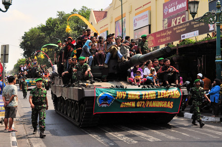 chock: Yogyakarta, Indonesia - 11 October 2014:  258th city anniversary - German Leopard 2 tanks are chock full with cvililians while running in a military parade to celebrate tradition and unity at Marlioboro Street, Kota Yogyakarta