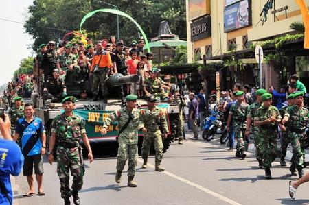 chock: Yogyakarta, Indonesia - 11 October 2014:  258th city anniversary - German Leopard 2 tanks are chock full with cvililians while running in a military parade to celebrate tradition and unity at Marlioboro Street, Kota Yogyakarta