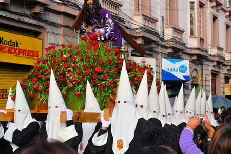 holy thursday: La Paz, Bolivia - 29 March 2013: Holy Thursday, traditional Easter procession in Spanish colonial Semana Santa style along Plaza Murillo. Penitents with traditional white hoods carry a statue of jesus christ, the savior. Bolivia is a very conservative cat