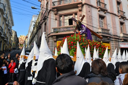 sinners: La Paz, Bolivia - 29 March 2013: Holy Thursday, traditional Easter procession in Spanish colonial Semana Santa style along Plaza Murillo. Penitents with traditional white hoods carry a statue of jesus christ, the savior. Bolivia is a very conservative cat
