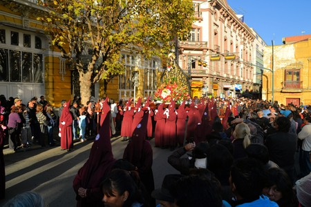 murillo: La Paz, Bolivia - 29 March 2013: Holy Thursday, traditional Easter procession in Spanish colonial Semana Santa style along Plaza Murillo. Penitents with traditional red hoods carry a statue virgin marx, mother of jesus christ. Bolivia is a very conservati
