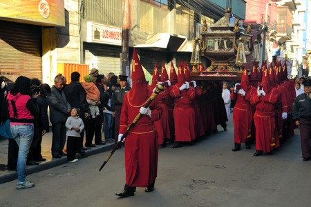 murillo: La Paz, Bolivia - 29 March 2013: Holy Thursday, traditional Easter procession in Spanish colonial Semana Santa style along Plaza Murillo. Penitents with traditional red hoods carry a statue of jesus christ, the savior. Bolivia is a very conservative catho