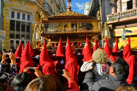 holy thursday: La Paz, Bolivia - 29 March 2013: Holy Thursday, traditional Easter procession in Spanish colonial Semana Santa style along Plaza Murillo. Penitents with traditional red hoods carry a statue of jesus christ, the savior. Bolivia is a very conservative catho