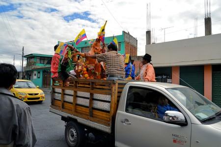 cavie: Latacunga, Ecuador 1 ottobre 2012: Un maiale ornata con frutta, liquori, bandiere e cavie viene trasportato da van a La Fiesta de la Mama Negra festa tradizionale. Mama Negra Festival è una miscela di influenze e ce indigeni, spagnoli e africani