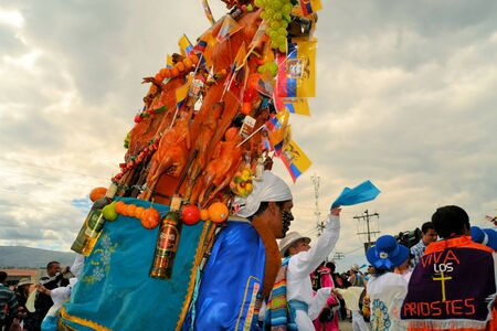 cavie: Latacunga, Ecuador 1 ottobre 2012: i partecipanti non identificati maiali parata ornati di frutta, liquori, bandiere e porcellini d'India a La Fiesta de la Mama Negra festa tradizionale. Mama Negra Festival è una miscela di influen indigeni, spagnoli e africani