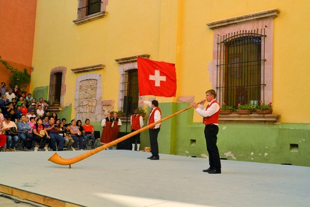alphorn: Zacatecas, Mexico, 01 August 2013: Unidentified musician from Switzerland plays a traditional alphorn on stage at the 18th Festival Cultural Internacional Zacatecas del Folclor. It is the biggest international folcloric festival of the Americas with troup