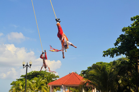 Playa del Carmen, Riviera Maya, Yucatan, Mexico - 19 August 2013: Acrobat performers, so-called Voladores, perform a Flying Men Dance ceremony near the beach of Playa del Carmen. The fertility ritual is a traditional Ceremony of Mayans and other tribes to