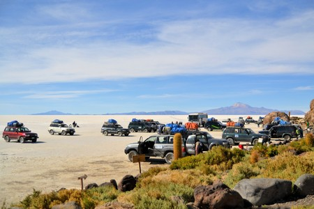 Salar Uyuni, Bolivia - 26 November 2012: Tourist Jeeps are stopping at Isla de Pescados in Salar Uyuni. A Jeep Tour through the Bolivian Salt Desert Uyuni is a popular touristic activity on the Altiplano in Bolivia