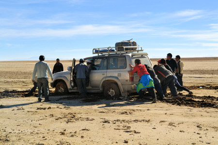 desert water: Uyuni, Bolivia - 28 November 2012: A tourist jeep gets stuck at Eduardo Avaroa National Park. Southwestern Bolivia is well-known for dramatic landscapes, lagunas, geysirs, desert and volcanoes
